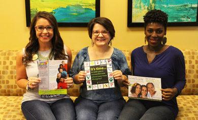 Three ladies holding marketing materials